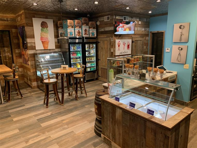 ice cream shop with wooden walls, 2 tables, 4 chairs and a glass refrigerator stocked with drinks and ice cream. Photos of ice cream cones and ice cream scoops on walls. Glass ice cream display case with ice cream cones and toppings displayed on top.