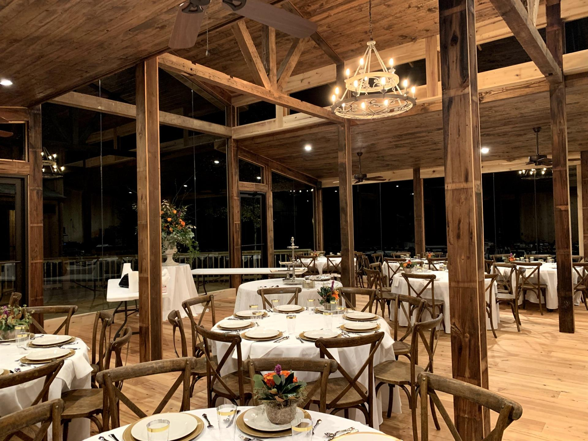 large room with floor to ceiling glass windows, wooden ceiling and columns. Multiple circle tables and chairs in the room with plates set