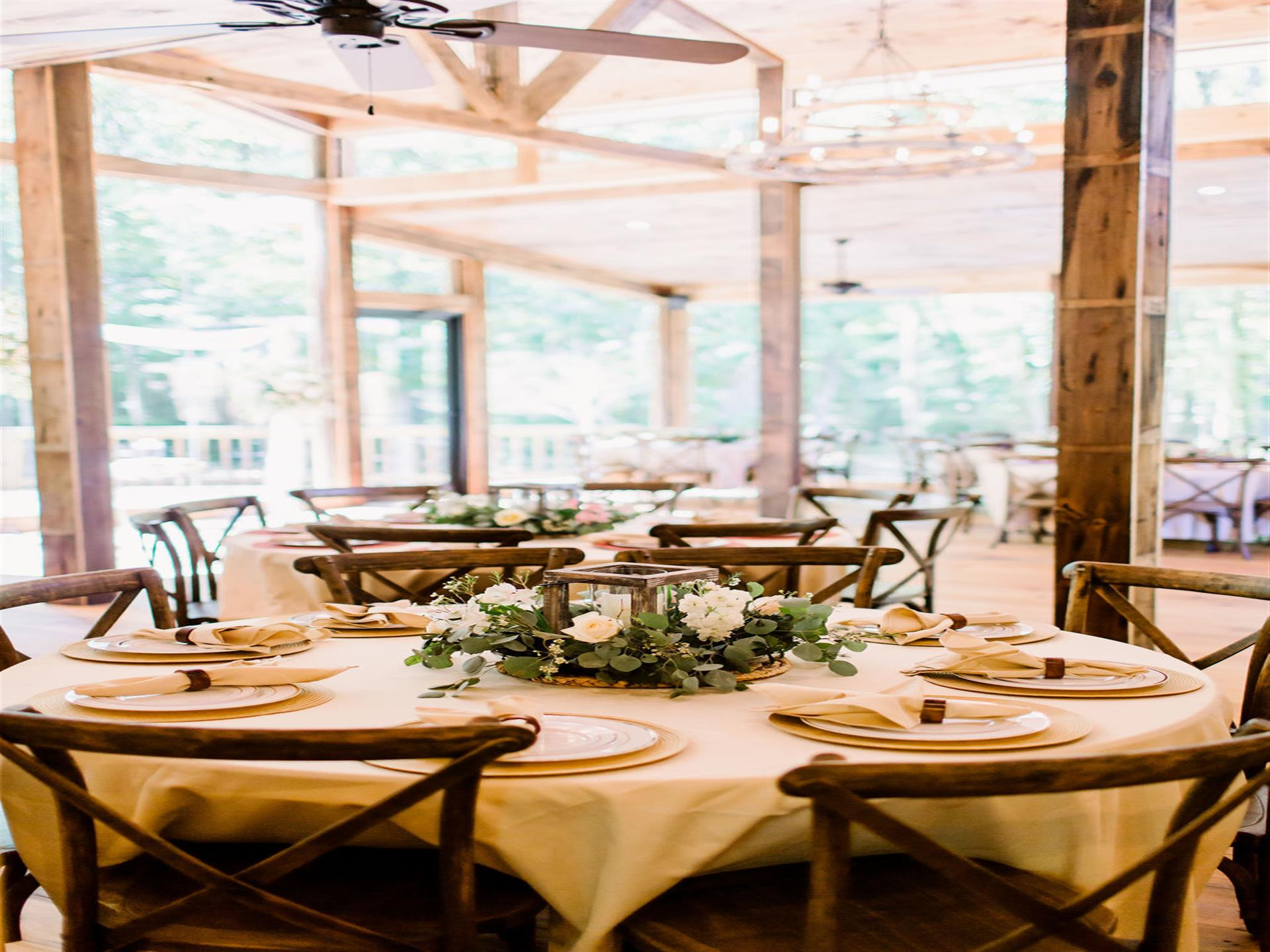 circular table with wooden chairs, table cloth and dining plates and napkins on top. flower display in the middle of table