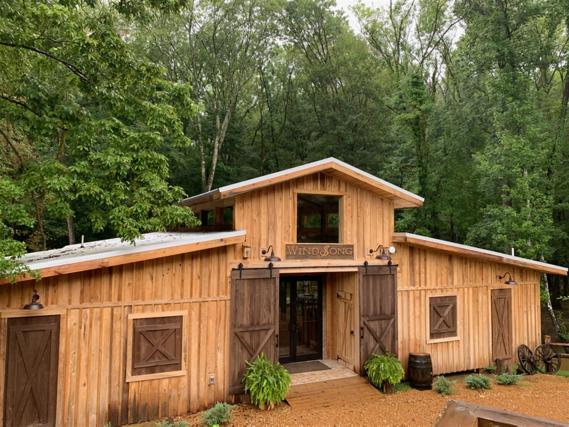 """wooden cabin with double doors, sign above doors that says """" WIND SONG"""" with the S as a treble clef. two shrubs next to the door and forest of trees in background."""