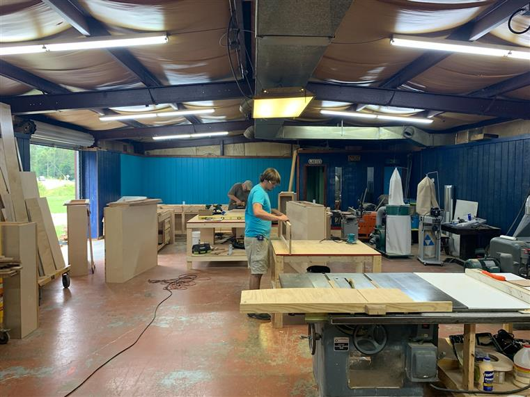 large woodshop room filled with wood pieces and tools. two men designing and working on wood furniture.