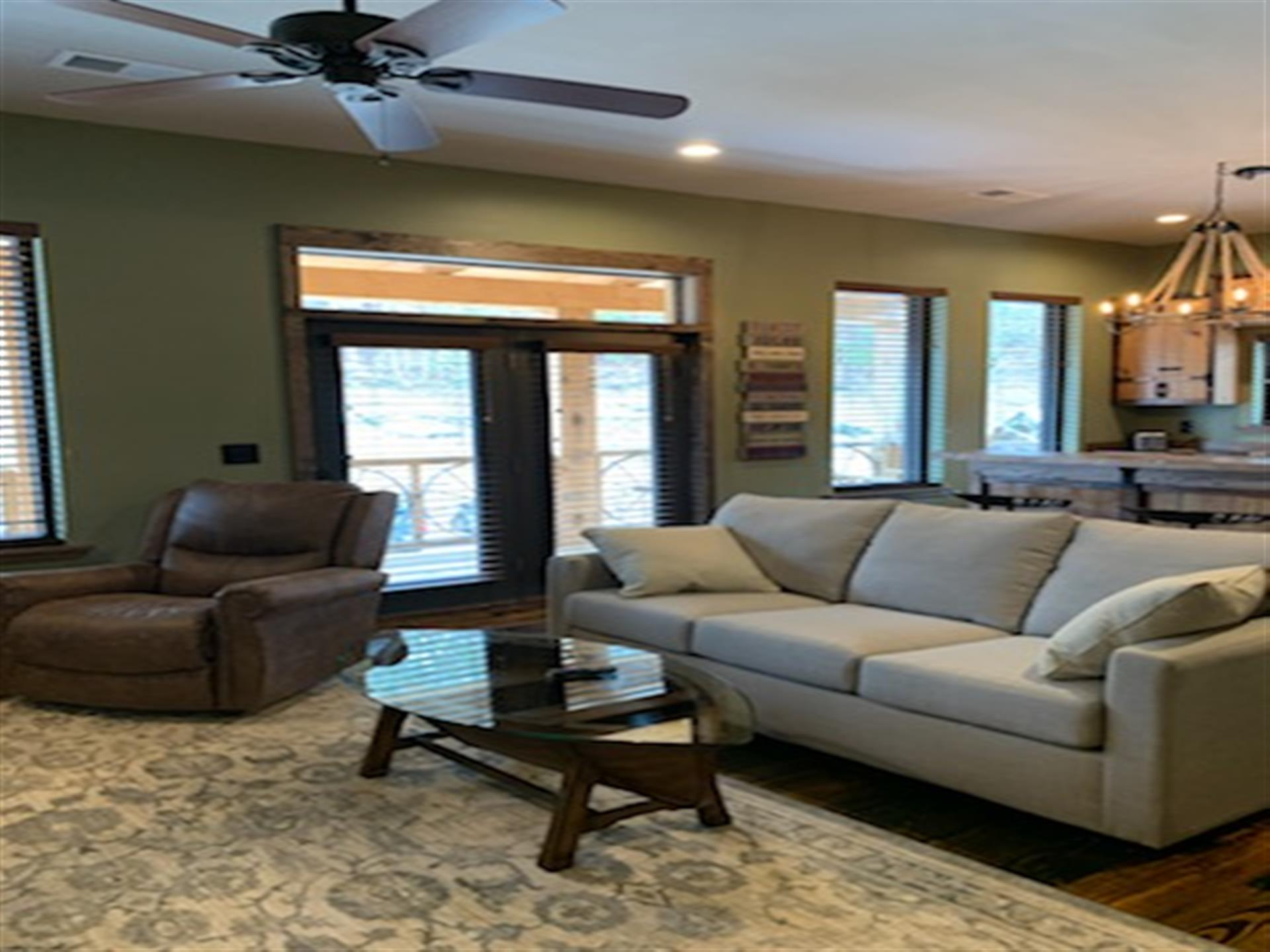 couch and single seat couch with glass table in front, ceiling fan above, doors and windows in background.