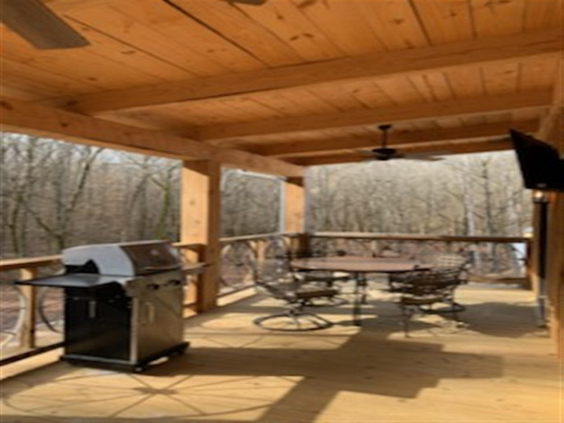 all wooden outside deck with grill and table with chairs and ceiling fan above. trees in the background