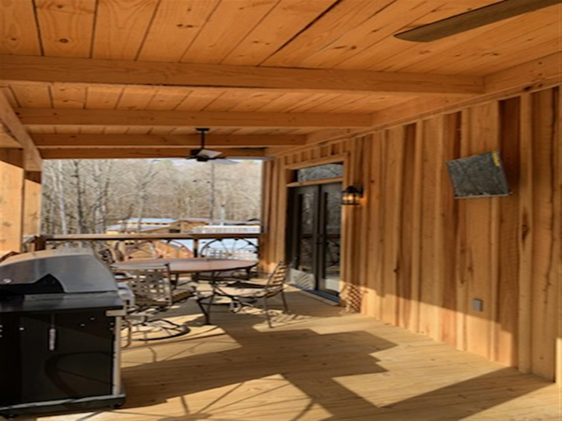 all wooden outside deck with wooden ceiling. circle table with chairs, fan above the table, tv on wall and grill to the left.