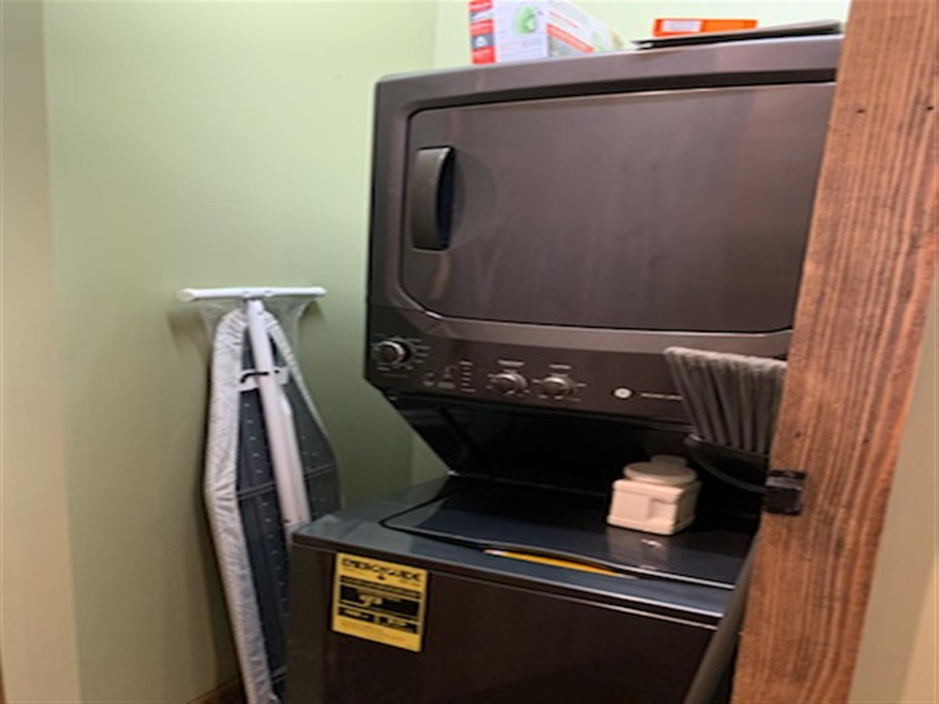 dryer on top of washer with iron board next to it against the wall
