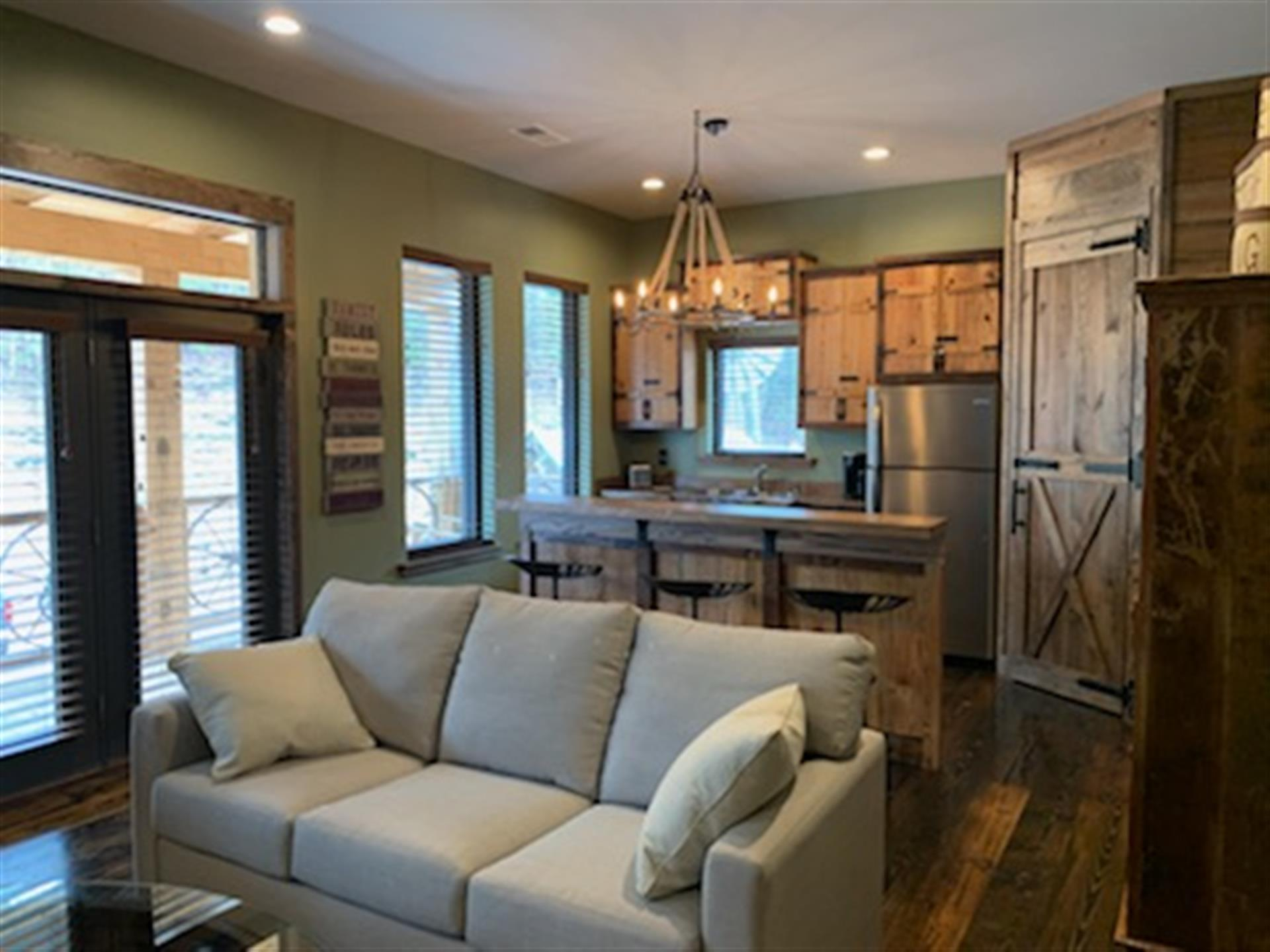 couch with double doors next to it. Kitchen in background with wooden cabinets and 3 stools at the countertop