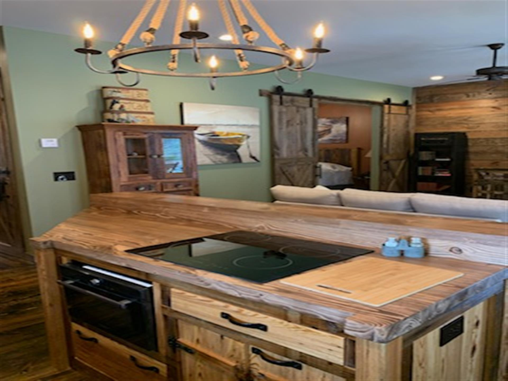 kitchen countertop with electric stove and light fixture above. living room with couch in background
