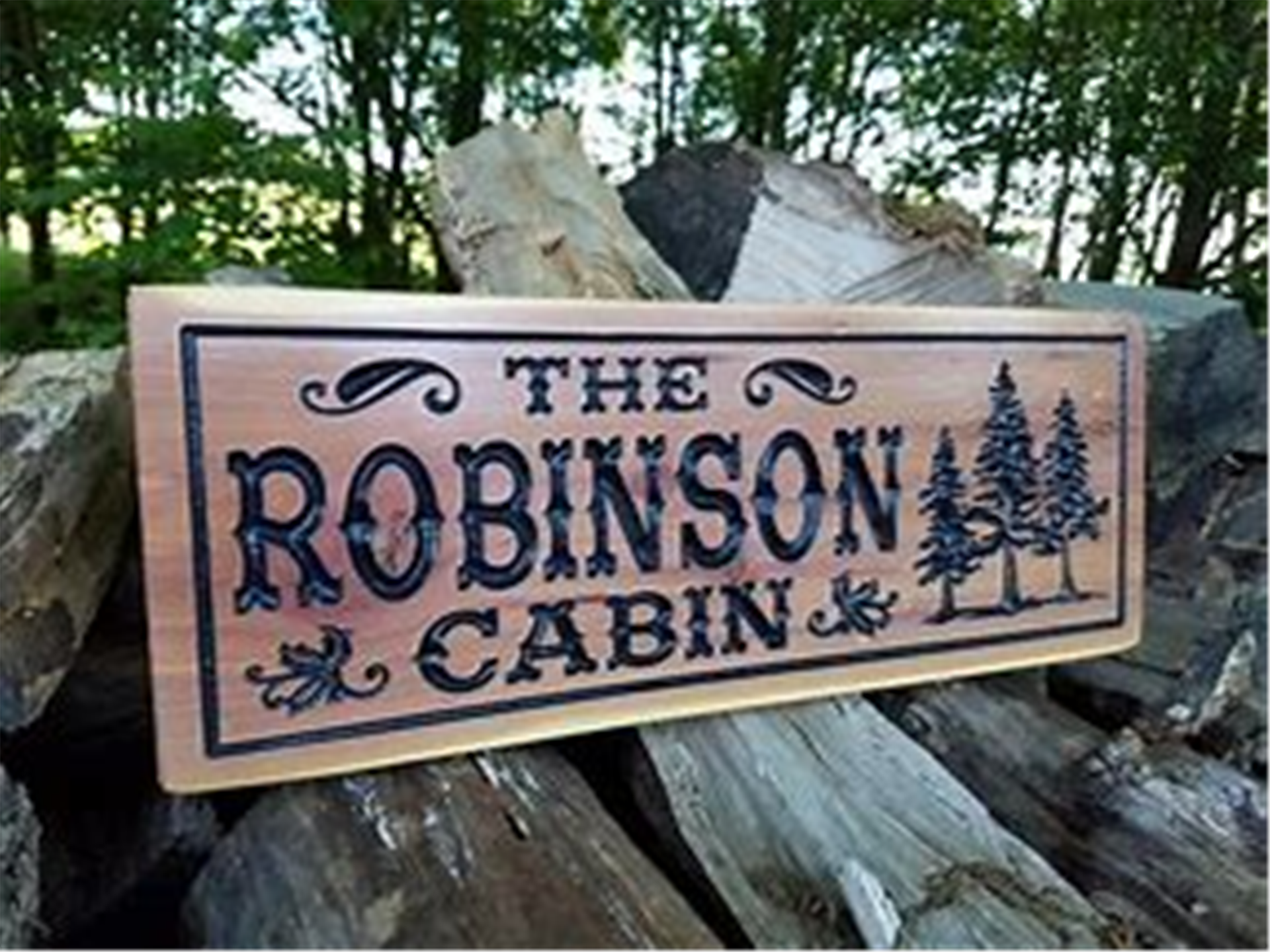 """rectangle wooden sign placed on top of wooden logs with trees in the background. """"THE ROBINSON CABIN"""" is engraved into the wooden sign along with 3 trees displayed next it."""