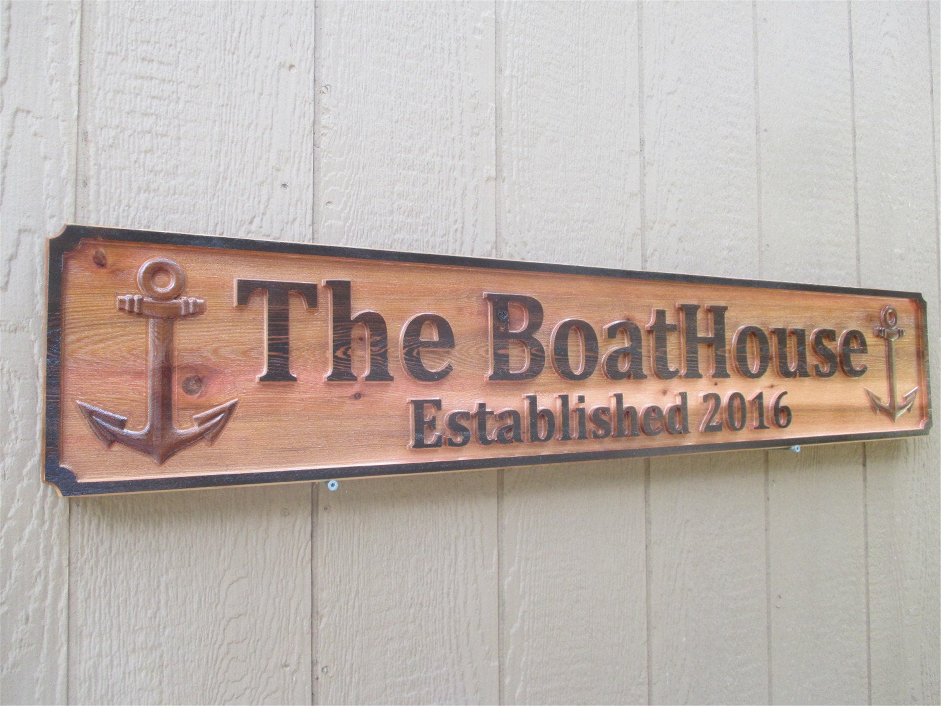 """wooden rectangle sign with """"The BoatHouse Established 2016"""" engraved between two anchors"""