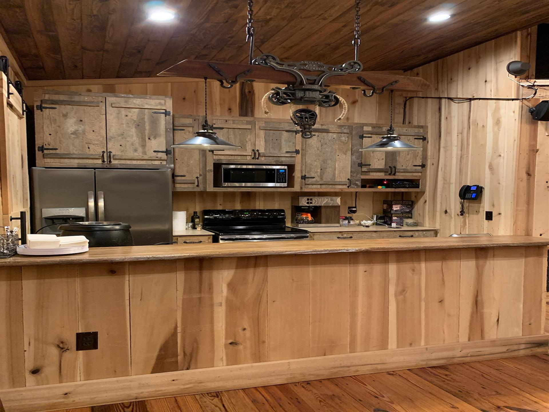 kitchen with wooden cabinets, wooden counter tops, wooden floors and ceiling. Light structure with two light fixtures above counter top hanging by metal chains