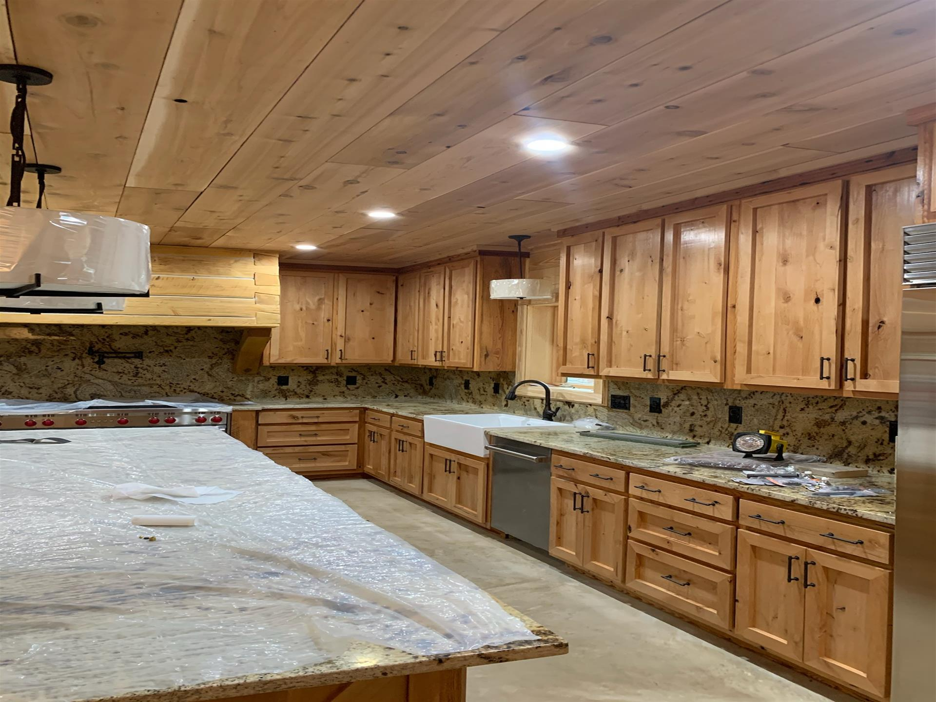 large open kitchen with wooden cabinets and drawers. Large island countertop with plastic cover on top
