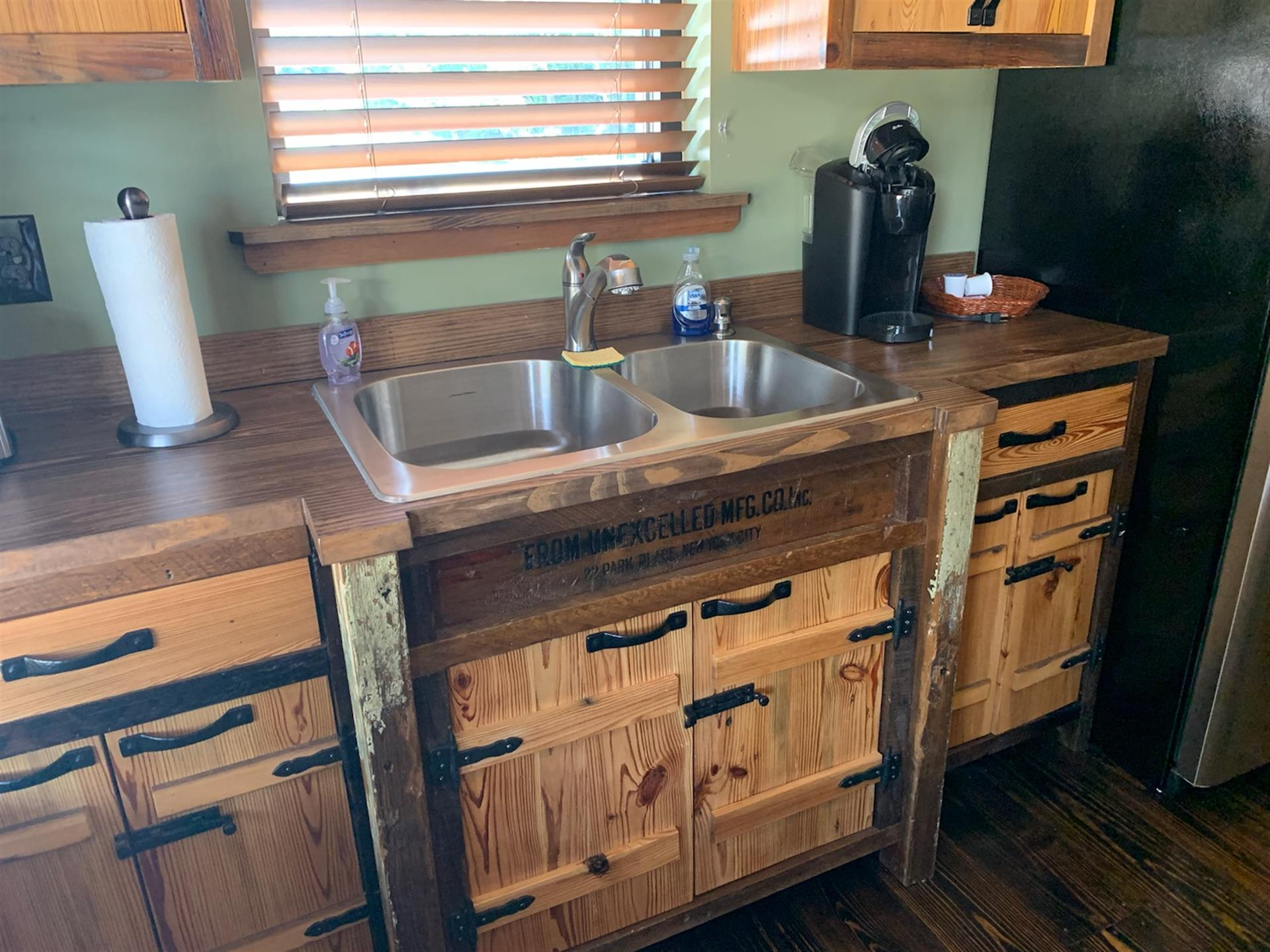 Wooden cabinets and drawers with one double bowl kitchen sink with window above, roll of paper towels to the left and coffee keurig to the right.