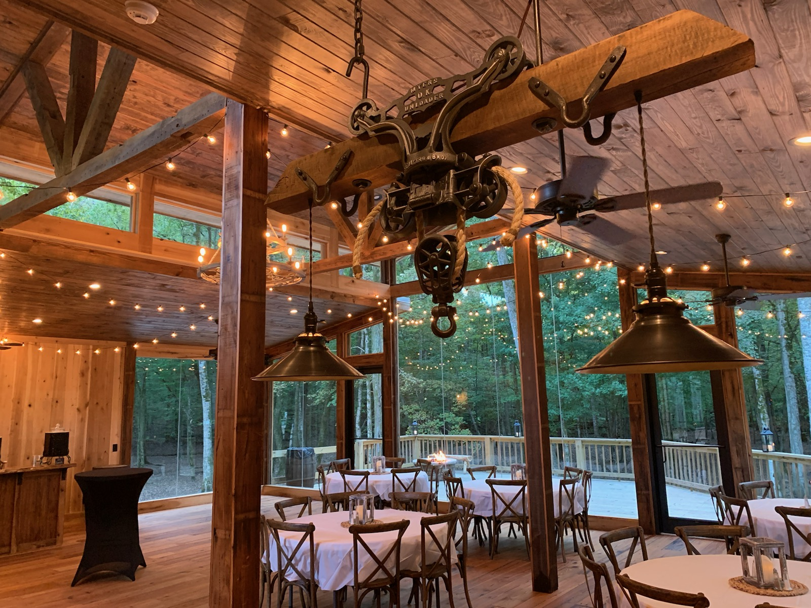 large room with floor to ceiling glass windows, wooden ceiling and columns. String lights hanging across the ceiling. Multiple circle tables with chairs and tablecloth on top