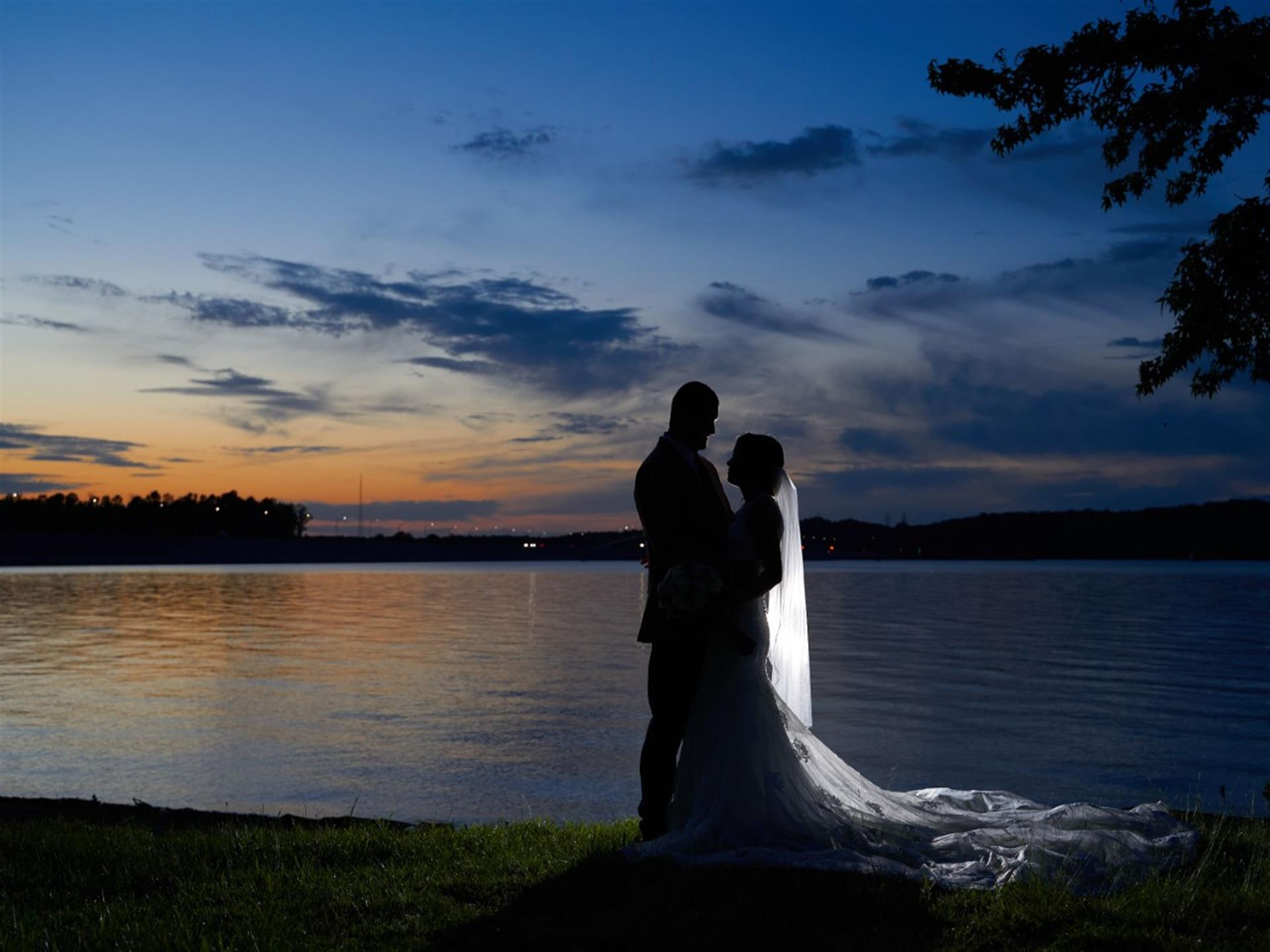 bride and groom on the beach looking into the sunset