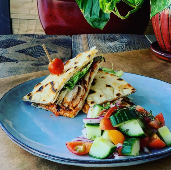 Veggie Naanwich with bell pepper, cucumber, red onion, zucchini, goat cheese, and garlic aioli and a side of vegetables