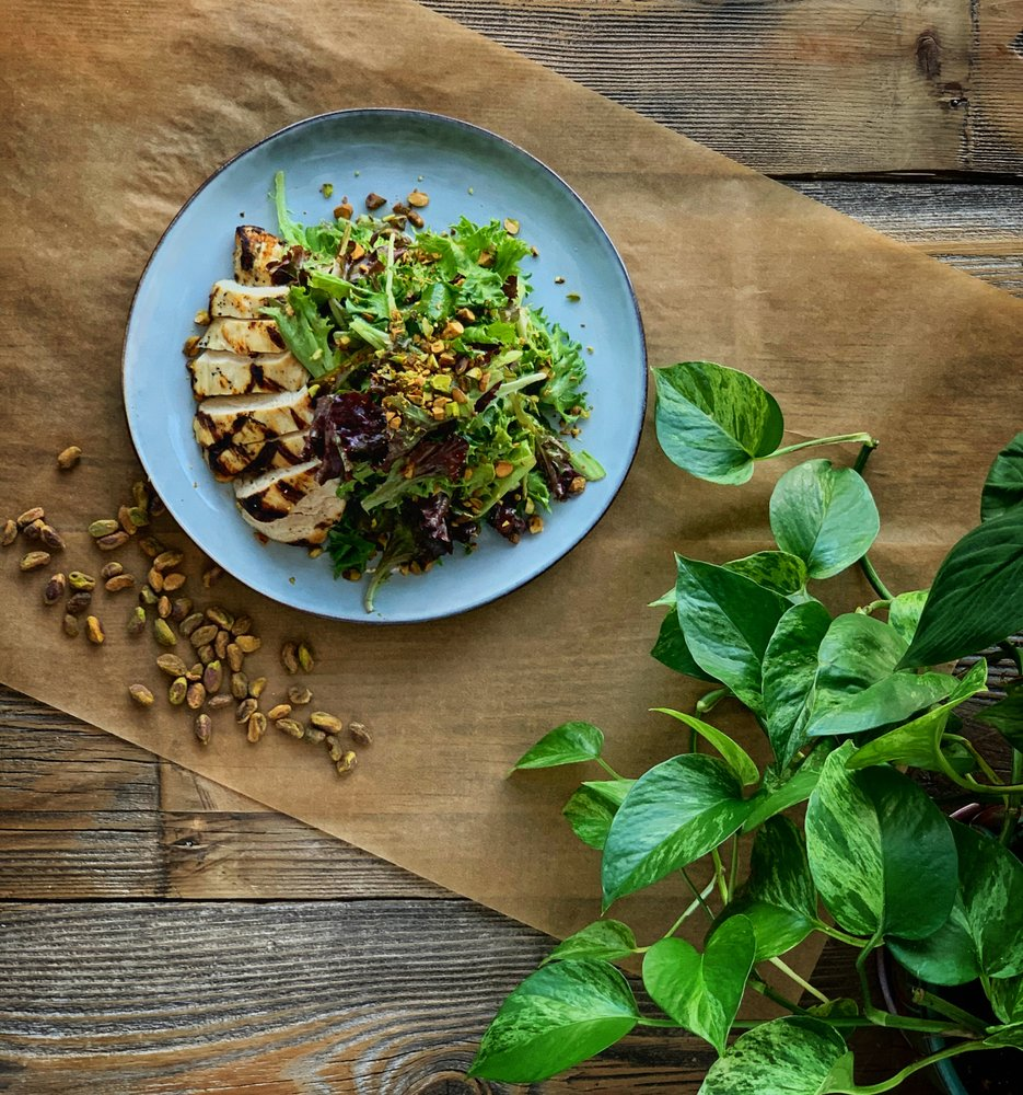 grilled chicken topped with mixed greens and pine nuts