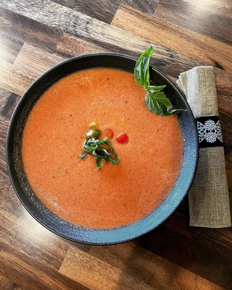 tomato soup in a bowl topped with garnish