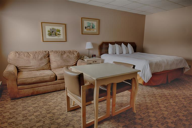 hotel room with a queen bed, a table and couch