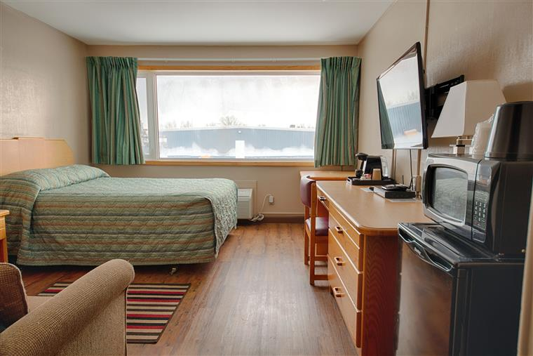 hotel room with a queen bed and a large window