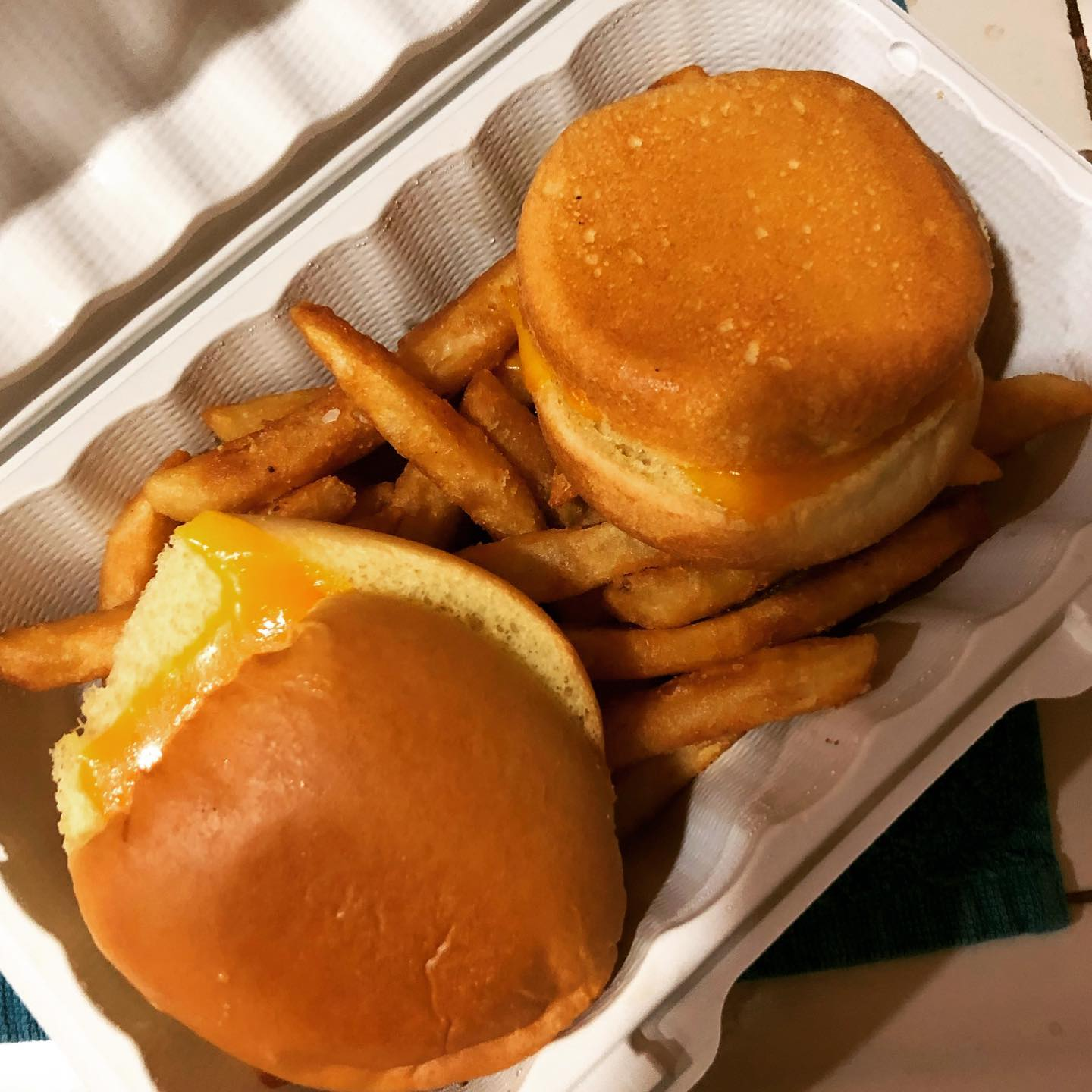 two grilled cheese on buns over fries in a to-go container
