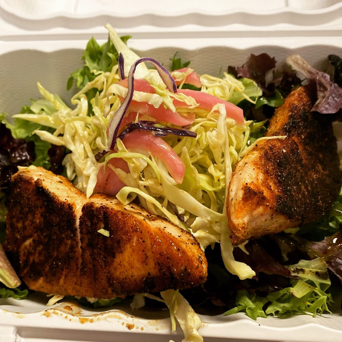grilled salmon on top of mixed greens
