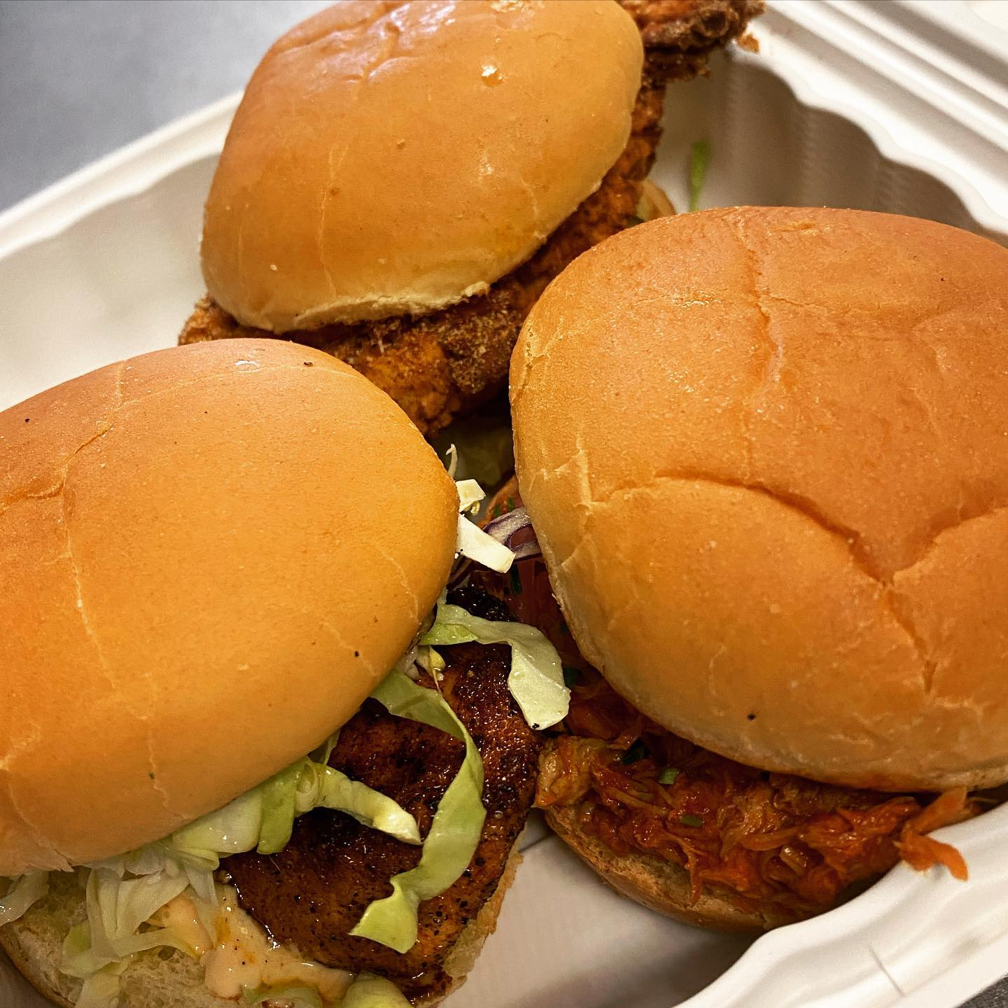 three chicken sandwiches topped with lettuce