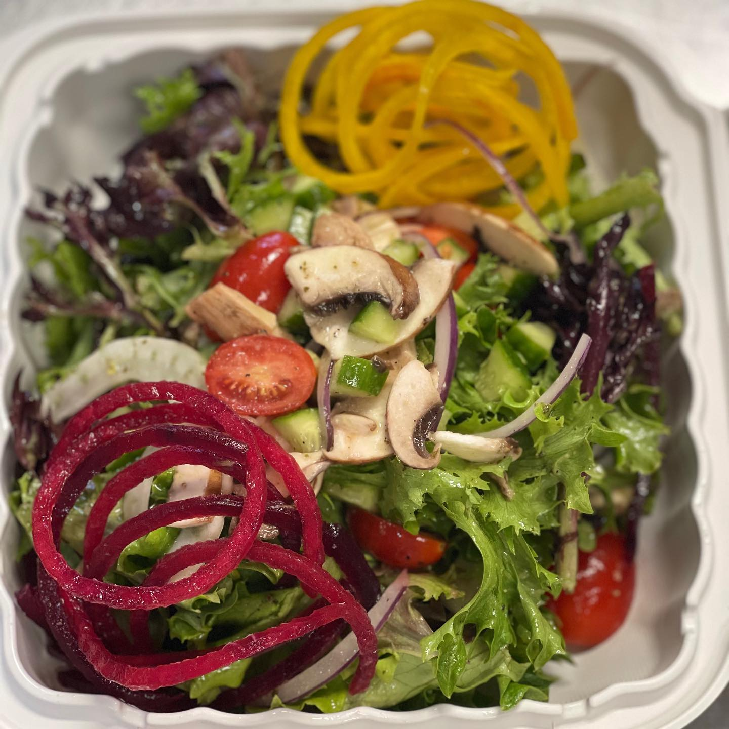 mixed greens topped with tomatoes, onions, mushrooms