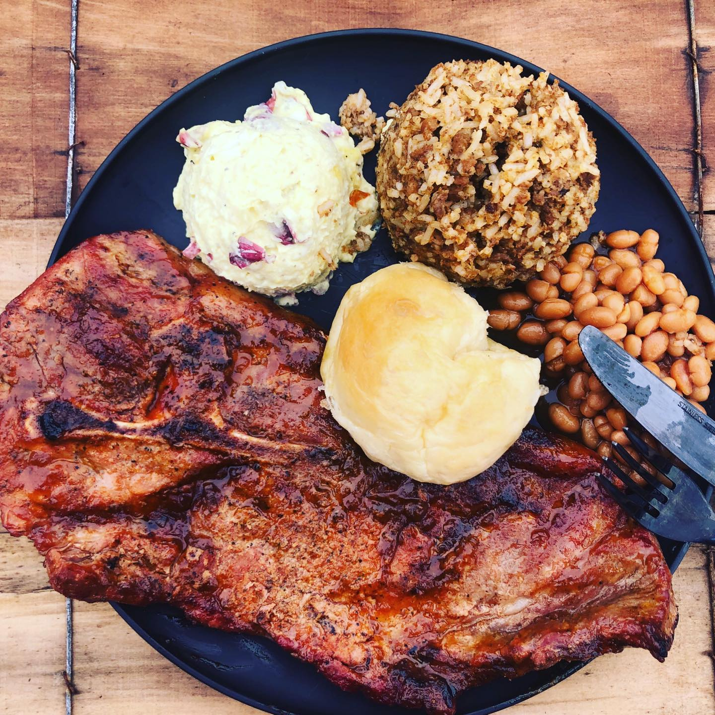 BBQ steak with mashed potatoes, potato salad and beans