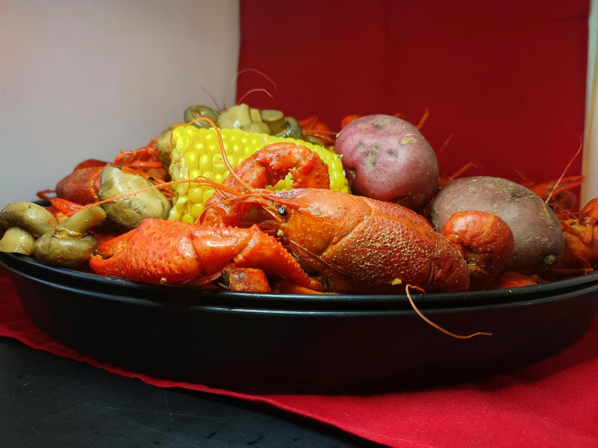 boiled crawfish served with corn, potatoes and mushrooms