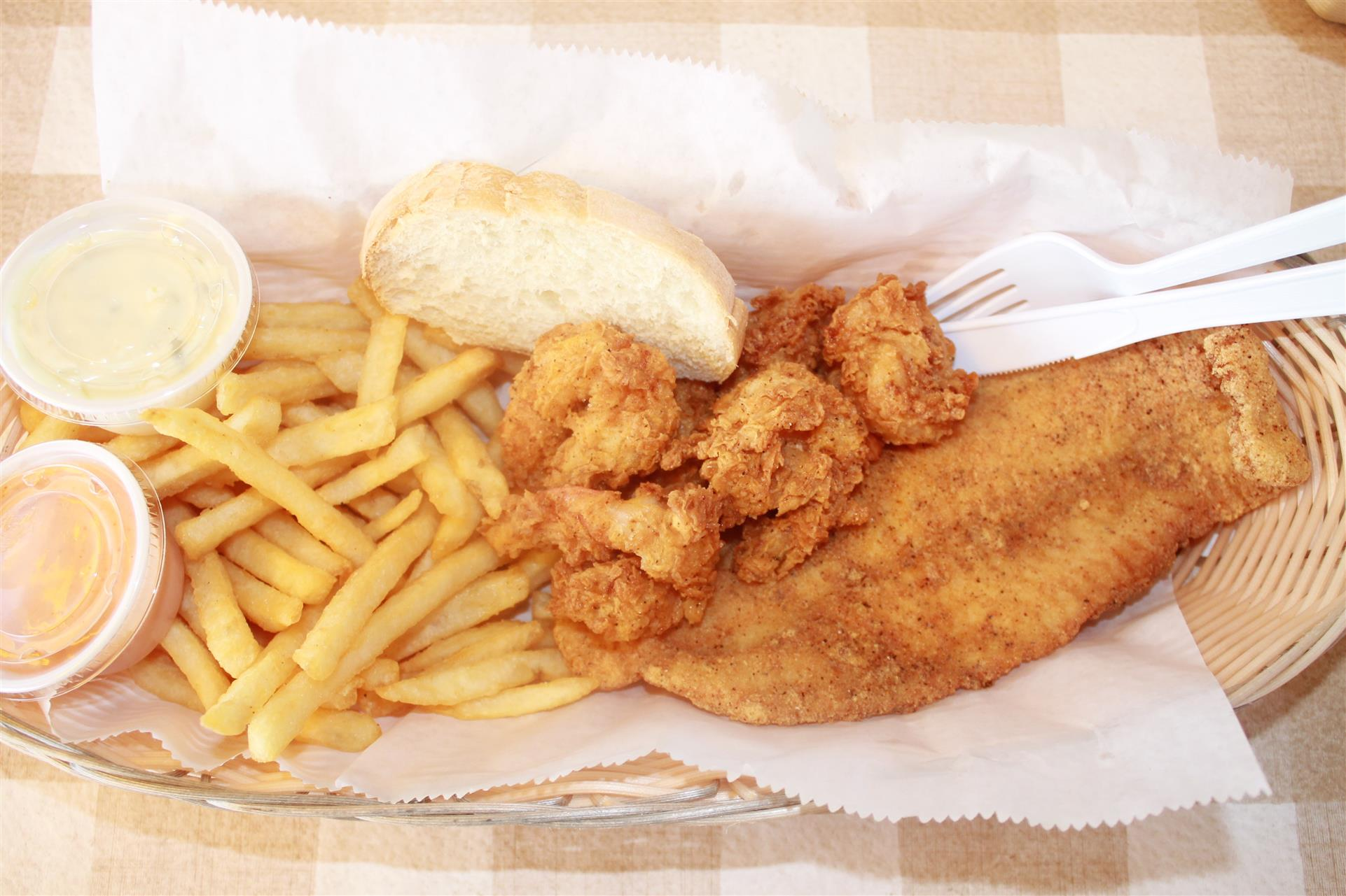 fried fish and shrimp in a basket with fries