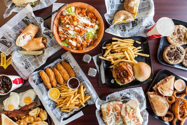 Sandwiches, chicken fingers,french fries and salad on a table
