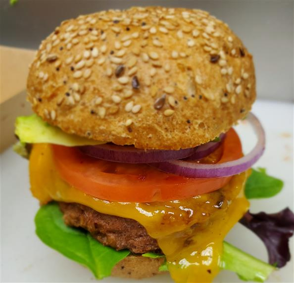 veggie burger with cheese, tomatoes, and onions
