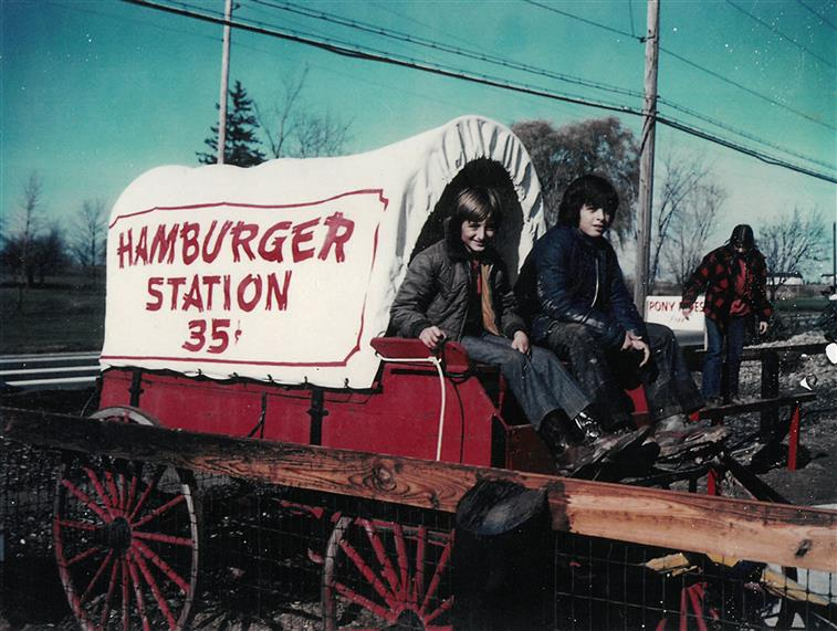 men in a hamburger station covered wagon