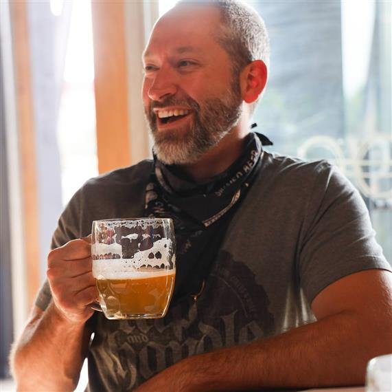 man holding a beer glass smiling