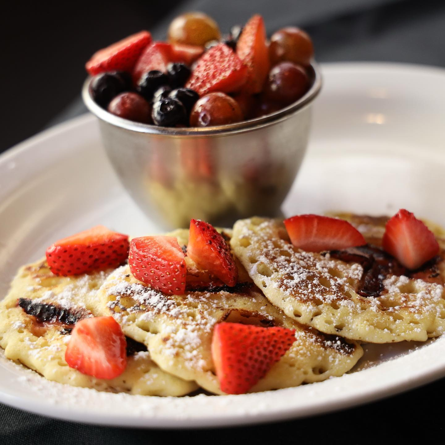 pancakes topped with strawberries and a side of fruit
