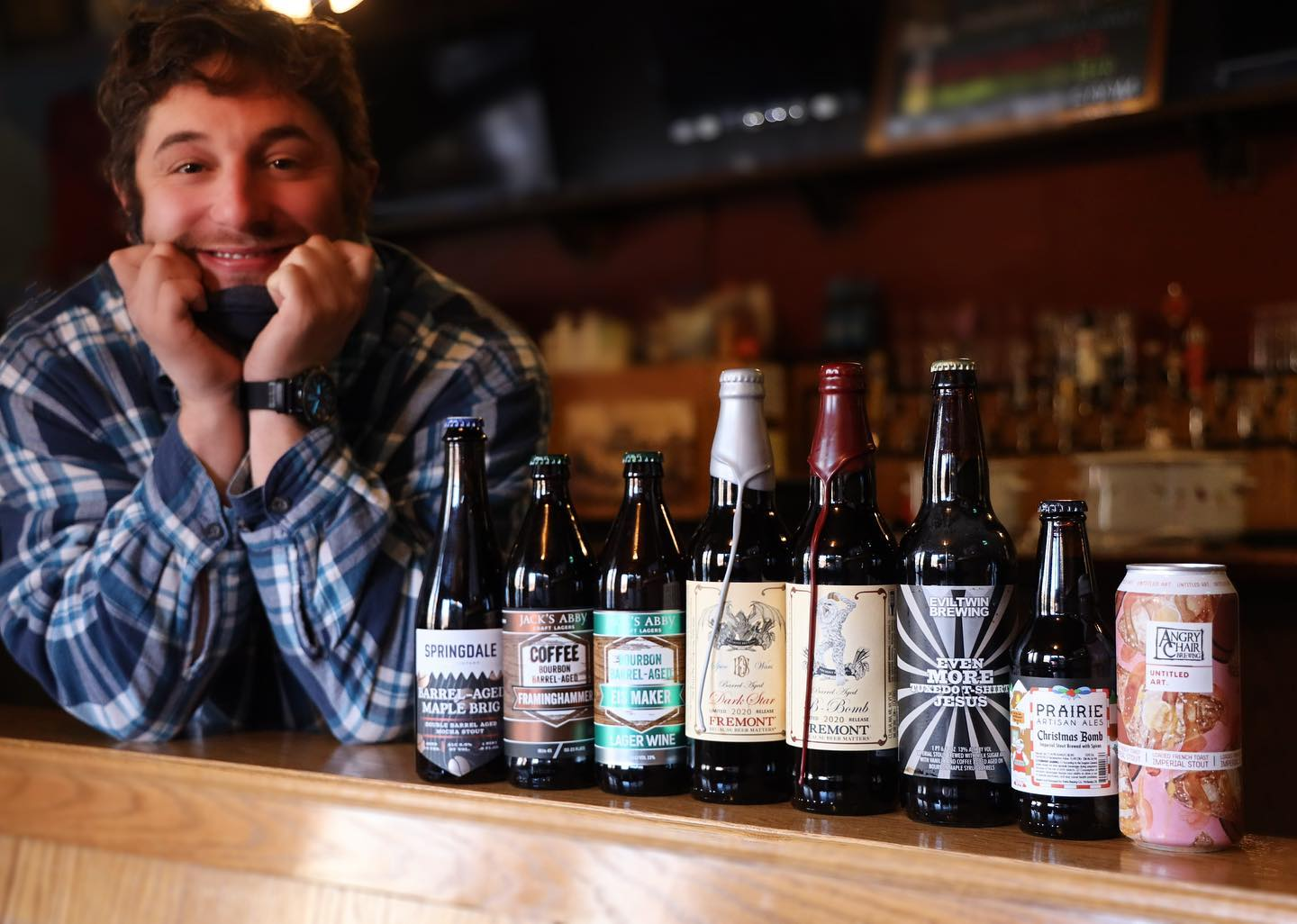 assortment of beer bottles infront of a man smiling