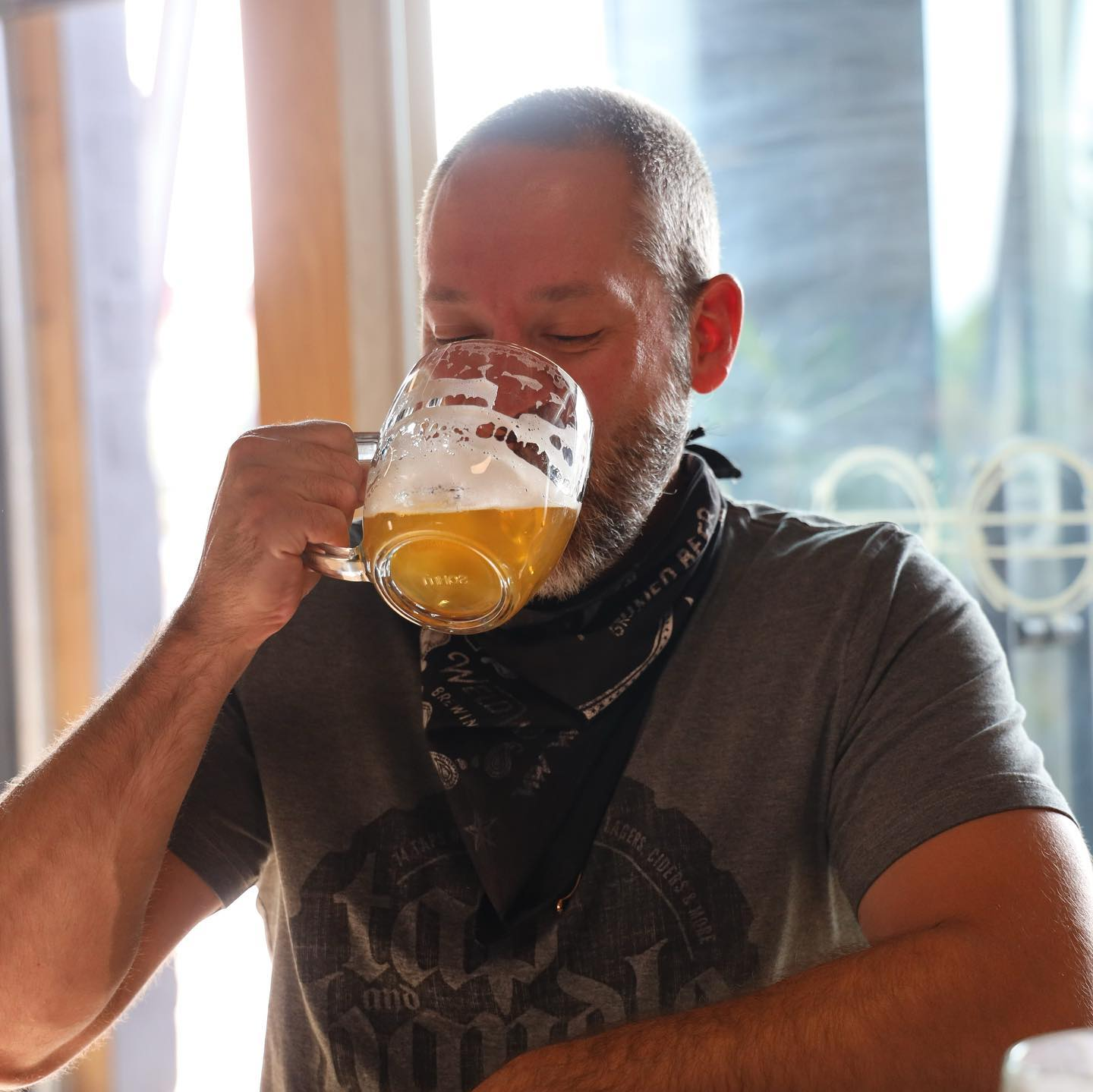 man drinking out of a beer mug