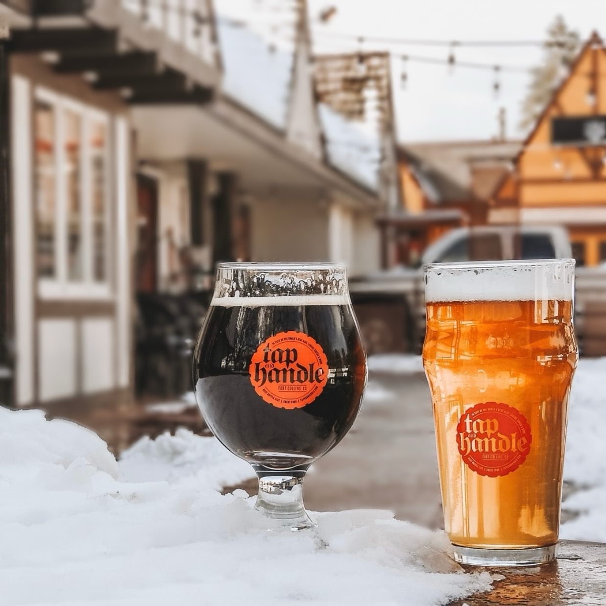 two beers in glasses in the snow outside