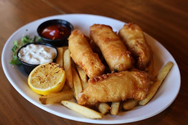 fish sticks over a bed of fries with a lemon wedge and dipping sauce