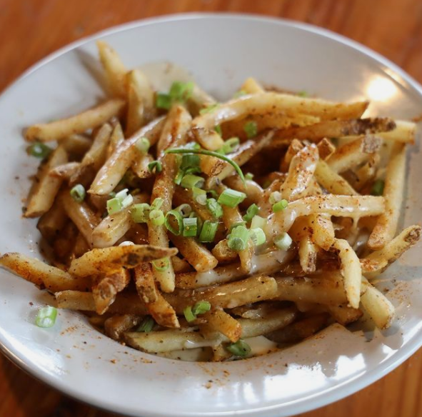 plate of fries topped with chives