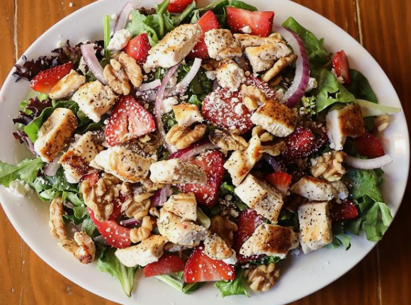 chicken salad topped with strawberries, red onion, and walnuts