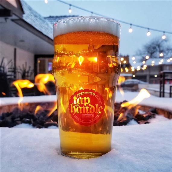 glass of beer outside in front of a firepit