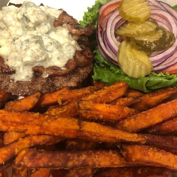 fried steak burger with cheese, mushrooms, lettuce, tomato and onions with sweet potato fries