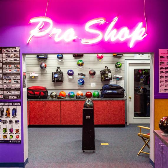 """entrance of the shop with """"pro shop"""" neon sign"""