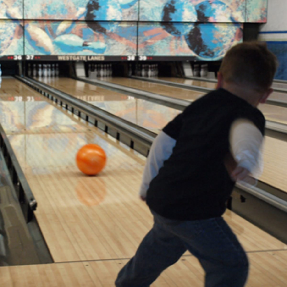 kid throwing a bowling ball down the lane