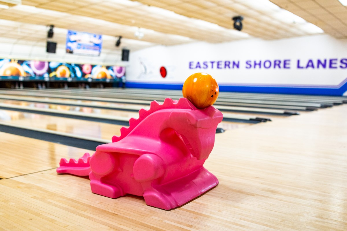 kid's bowling ramp shaped like a dinosaur with bowling ball on top