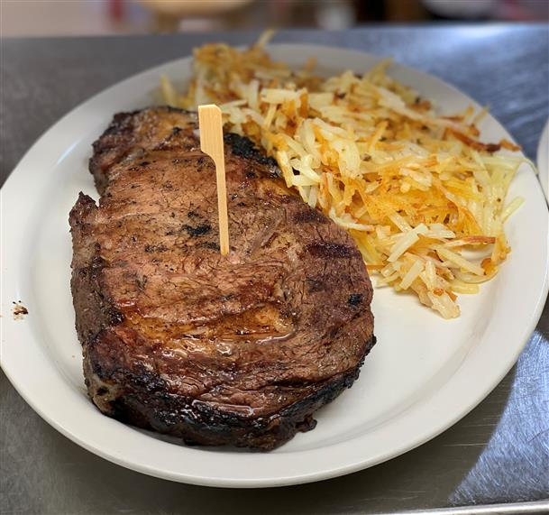 grilled steak with a side of hashbrowns