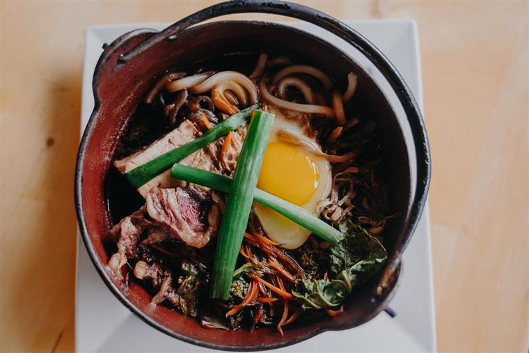 udon noodle bowl with pork, greens, carrots, egg and chive shoots