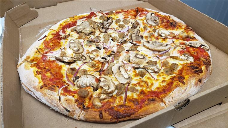pizza pie topped with sausage, onions, and mushrooms