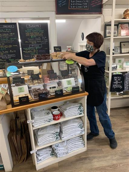 woman fixing a display at the fudge counter